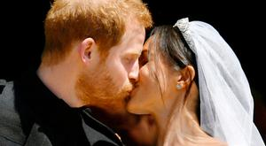 Prince Harry and Meghan Markle kiss on the steps of St George's Chapel in Windsor Castle after their wedding. PRESS ASSOCIATION Photo.