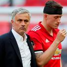 Manchester United's Phil Jones looks dejected after losing the FA Cup final with manager Jose Mourinho. REUTERS/David Klein