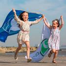 Caoimhe (7) and Alannah Culhane (5) celebrate the awarding of the International Blue Flag award for 2018 at Seapoint, Co Dublin. Photo: Naoise Culhane