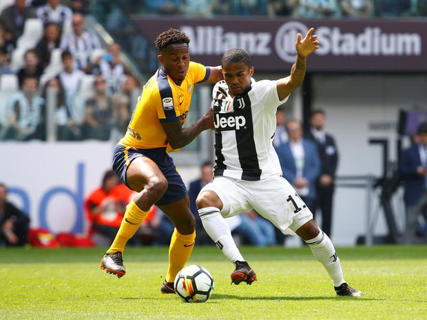 Juventus' Douglas Costa in action with Hellas Veronas Rolando Aarons REUTERS/Stefano Rellandini