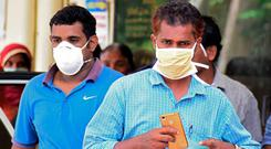 Indian residents wear face mask outside the Medical College hospital in Kozhikode on May 21, 2018. AFP PHOTO / --/AFP/Getty Images