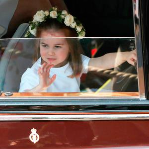 Princess Charlotte waves as she leaves St George's Chapel at Windsor Castle following the wedding of her uncle Prince Harry to Megan Markle