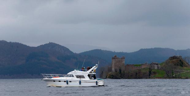 A boat sails in front of Urquhart Castle on Loch Ness in Scotland Britain