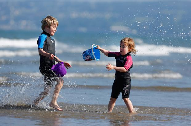 Juliette Orr (3) and her brother Hugo (6), from Portmarnock, making a splash on Portmarnock Strand in Dublin yesterday. Photos: Damien Eagers