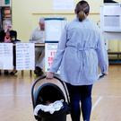 A woman arrives to vote carrying a baby as Ireland holds a referendum on liberalising its law on abortion. REUTERS/Max Rossi