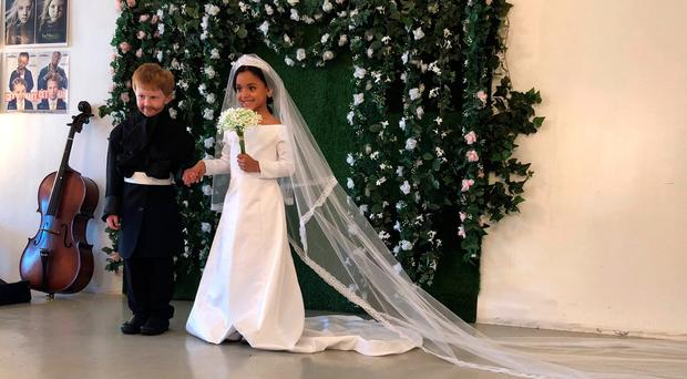 Six year-old Andrew Robert dressed as Prince Harry and seven-year-old Naiyah Otero dressed as Meghan Markle pose during a photo shoot at Toddlewood Studio in Baldwin, New York, U.S., May 23, 2018. Photo taken May 23, 2018. REUTERS/Roselle Chen