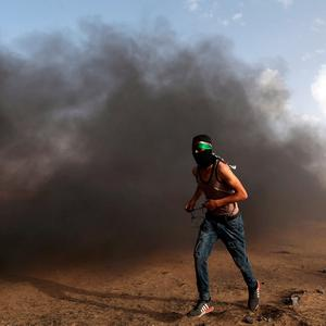 A demonstrator runs during a protest where Palestinians demand the right to return to their homeland, at the Israel-Gaza border in the southern Gaza Strip May 25, 2018. REUTERS/Ibraheem Abu Mustafa