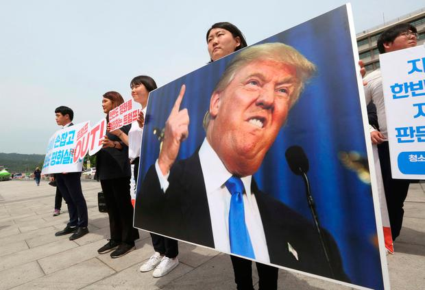 Protesters with a portrait of US President Donald Trump stage a rally against the United States' policies near the US embassy in Seoul, South Korea, yesterday. Photo: AP