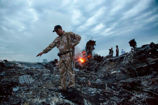 In this 2014 file photo, people walk among the debris at the crash site of Malaysia Airlines Flight 17. Image: AP Photo/Dmitry Lovetsky.