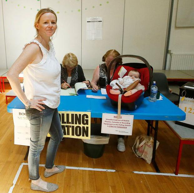 Nicola Faherty, with baby Freya Molloy, from Greystones, casting her vote at Delgany National School, Co Wicklow. Photo: Stephen Collins/Collins Photos