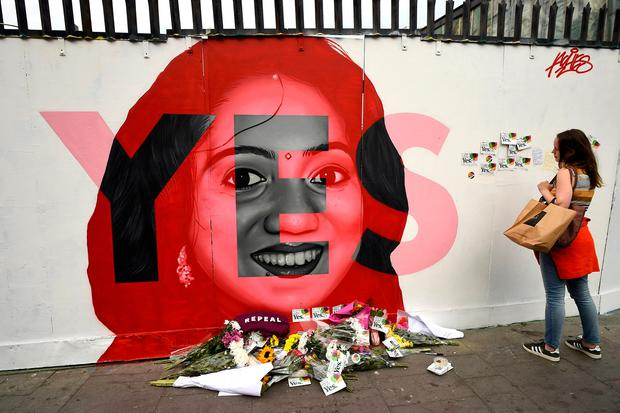 A woman looks at a new mural of Savita Halappanavar with flowers placed beneath it put up on the day of the Abortion Referendum. REUTERS/Clodagh Kilcoyne