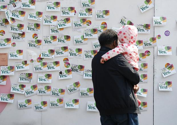 A man and his child look at messages in memory of Savita Halappanavar, beside a mural of her on South Richmond Street in Dublin, she was a 31-year-old Indian dentist who died in 2012 at University Hospital Galway in Ireland due to complications arising from a septic miscarriage. Picture credit; Damien Eagers