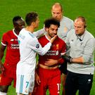 Liverpool's Mohamed Salah reacts with Sadio Mane and Real Madrid's Cristiano Ronaldo as he is substituted after sustaining an injury