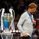 Liverpool manager Jurgen Klopp walks past the Champions League trophy
