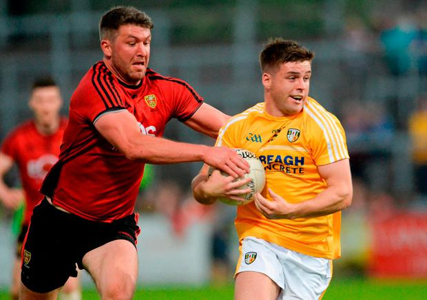 Patrick McBride of Antrim in action against Peter Turley of Down. Photo: Oliver McVeigh/Sportsfile