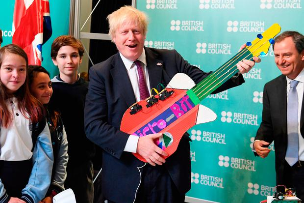 CHILE RECEPTION: Boris Johnson plays an electronic guitar made by children being taught coding by the British Council in Santiago. Photo: Stefan Rousseau/PA Wire