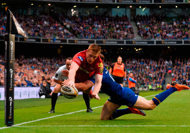 Johnny McNicholl of Scarlets scores his side's first try despite the tackle from Garry Ringrose. Photo: David Fitzgerald/Sportsfile