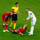 Liverpool's Mohamed Salah after sustaining an injury while Liverpool's Roberto Firmino looks on and Real Madrid's Sergio Ramos talks with referee Milorad Mazic