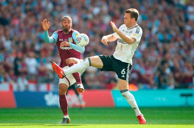 Aston Villa's Lewis Grabban (left) and Fulham's Kevin McDonald battle for the ball. Photo credit: John Walton/PA Wire