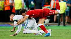 Sergio Ramos tangles with Mo Salah in the incident which saw the Liverpool star injure his left shoulder. Photo: Reuters/Gleb Garanich