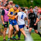 Referee Paud O'Dwyer calls for order as Jamie Barron of Waterford and Clare's David Fitzgerald jostle. Photo: Ray McManus/Sportsfile