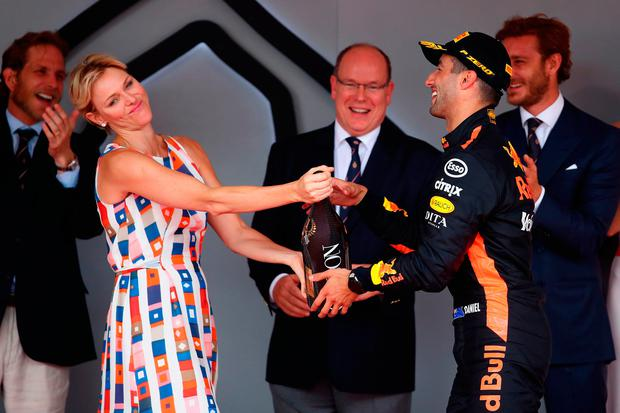 Race winner Daniel Ricciardo of Australia and Red Bull Racing shares his champagne with Princess Charlene of Monaco on the podium during the Monaco Formula One Grand Prix at Circuit de Monaco on May 27, 2018 in Monte-Carlo, Monaco. (Photo by Mark Thompson/Getty Images)