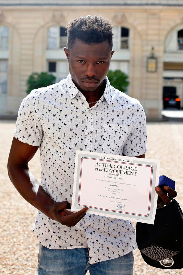 Mamoudou Gassama, 22, from Mali, displays a certificate of courage and dedication signed by Paris Police Prefect Michel Delpuech as he leaves the Elysee Palace after his meeting with French President Emmanuel Macron, in Paris, France, May 28, 2018.Thibault Camus/Pool via Reuters