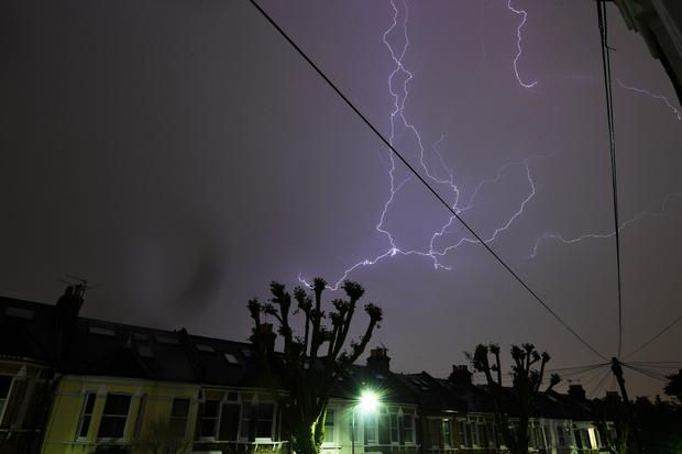 Lightning is seen from a bedroom window as it strikes above a street in south London, Britain May 26, 2018. REUTERS/Dylan Martinez