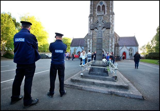 Gardai gather amongst mourners at St. Brigid's Church in Dunleer for the Vigil for Cameron Reilly whose body was found at the weekend. Photo: Steve Humphreys