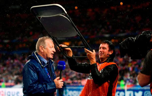 RTE's Tony O'Donoghue is sheltered from the rain. Photo: Stephen McCarthy/Sportsfile