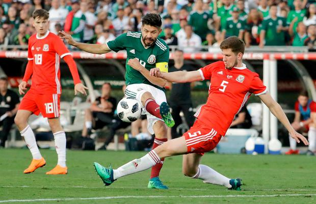 Wales' Chris Mepham, right, tackles Mexico's Oribe Peralta