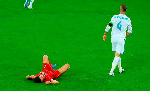 Liverpool's Mohamed Salah (left) lies injured on the pitch after a challenge from Real Madrid's Garcia Sergio Ramos during the UEFA Champions League Final at the NSK Olimpiyskiy Stadium, Kiev. Peter Byrne/PA Wire