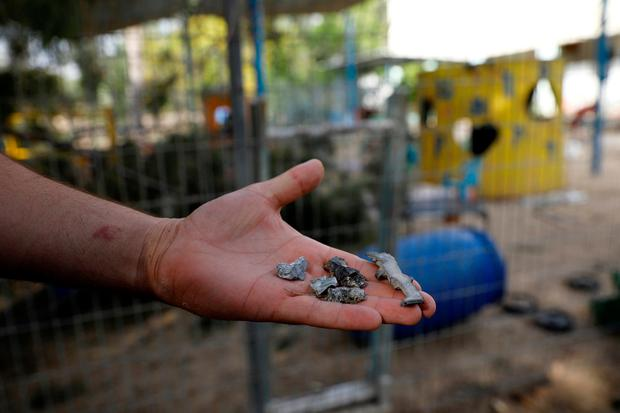 A man holds shrapnel from mortar shells fired from the Gaza Strip that landed near a kindergarten, in a Kibbutz on the Israeli side of the Israeli-Gaza border, May 29, 2018. REUTERS/Amir Cohen
