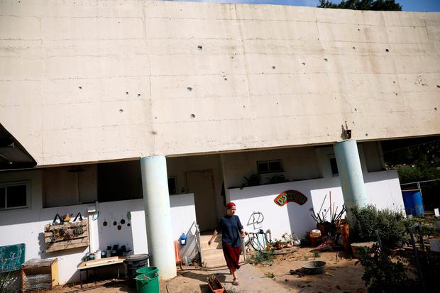 A woman walks out of a kindergarten, where damages caused by mortar shells fired from the Gaza Strip that landed near it, can be seen on its wall, in a Kibbutz on the Israeli side of the Israeli-Gaza border May 29, 2018. REUTERS/Amir Cohen