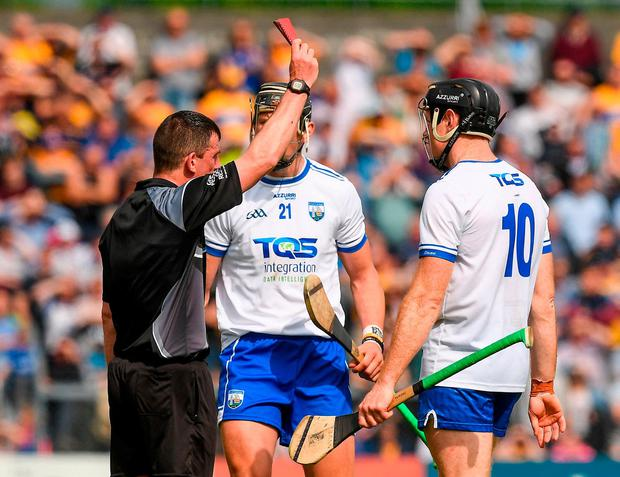 Referee Paud O'Dwyer issues a red card to Kevin Moran who'll sit out Sunday's clash against Tipperary due to the resulting suspension. Photo: Ray McManus/Sportsfile