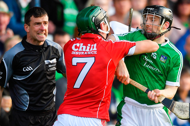 Cork's Mark Coleman and Limerick's Graeme Mulcahy tangle as linesman Paud O'Dwyer looks on. Photo: Sportsfile
