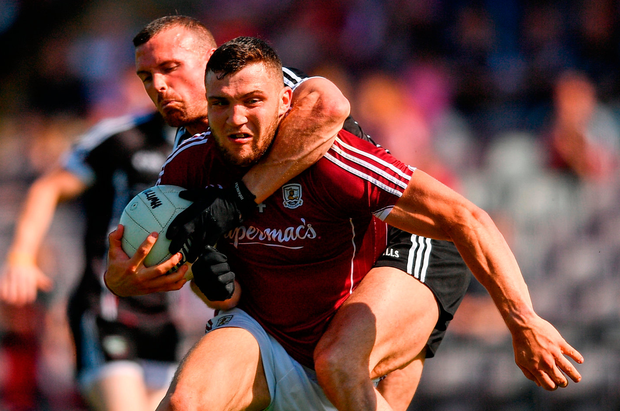 Sligo's Eoin McHugh attempts to get to grips with Galway's Damien Comer at Pearse Stadium. Photo: Sportsfile