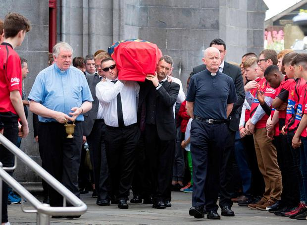Fr Tom Hogan with mourners as they carry the coffin of Jack Kenneally draped with a Munster flag as Ennis Rugby Club members provide a guard of honour at Ennis Cathedral yesterday