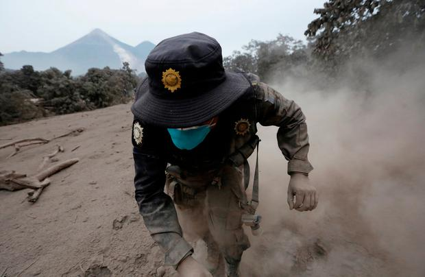 A police officer stumbles while running away after the Fuego volcano spew new pyroclastic flow in the community of San Miguel Los Lotes in Escuintla, Guatemala, June 4, 2018. REUTERS/Luis Echeverria TPX IMAGES OF THE DAY