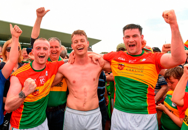 Sporting his scars of battle, Paul Broderick (centre) celebrates Carlow's victory over Kildare with Cian Lawler and John Murphy. Photo: Matt Browne/Sportsfile