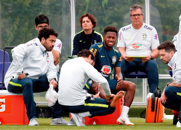 Brazil's Fred receives medical attention during training