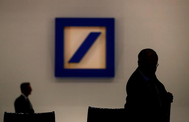 Paul Achleitner is silhouetted next to the Deutsche Bank logo prior to the bank's annual meeting in May. Photo: REUTERS/Kai Pfaffenbach/File Photo