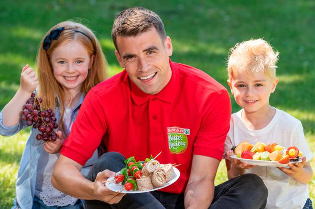 Seamus Coleman gets ready to tuck into some healthy eating with Sophie Bracken (5) and Alex Donoghue (6) at the launch of SPAR's Better Choices summer recipes. Photo: Naoise Culhane