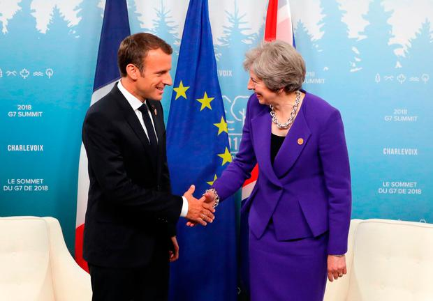 French President Emmanuel Macron shakes hands with British Prime Minister Theresa May at the G7 Summit. Photo: Getty Images