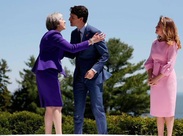 British Prime Minister Theresa May is greeted by Canadian Prime Minister Justin Trudeau and his wife Sophie Gregoire Trudeau, during the G7 Summit, Friday, June 8, 2018, in Charlevoix, Canada. (AP Photo/Evan Vucci)