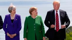 Britain's Prime Minister Theresa May, Germany's Chancellor Angela Merkel and U.S. President Donald Trump pose during a family photo at the G7 Summit in the Charlevoix city of La Malbaie, Quebec, Canada, June 8, 2018. REUTERS/Yves Herman