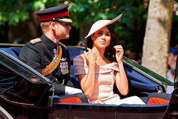Britain's Prince Harry, Duke of Sussex and Britain's Meghan, Duchess of Sussex travel in a horse-drawn carriage down The Mall to Horseguards parade ahead of the Queen's Birthday Parade, 'Trooping the Colour', in London on June 9, 2018