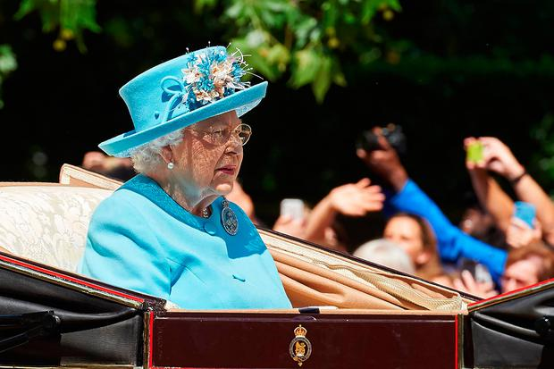Britain's Queen Elizabeth II travels in a horse-drawn carriage down The Mall to Horseguards parade ahead of her Birthday Parade, 'Trooping the Colour', in London on June 9, 2018
