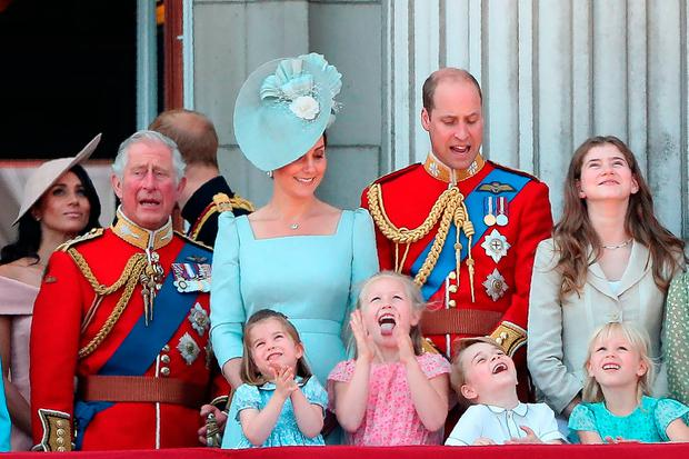 Members of the Royal Family (L-R) Britain's Meghan, Duchess of Sussex, Britain's Prince Charles, Prince of Wales, Britain's Catherine, Duchess of Cambridge (with Princess Charlotte and Prince George) and Britain's Prince William, Duke of Cambridge, stand on the balcony of Buckingham Palace to watch a fly-past of aircraft by the Royal Air Force, in London on June 9, 2018