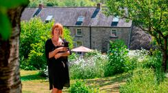 Jadzia Kaminska in the garden of Mill Cottage which comprises a thatched cottage and adjoining stone farmhouse.